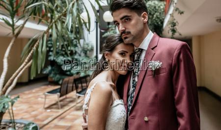 portrait of groom embracing beautiful bride