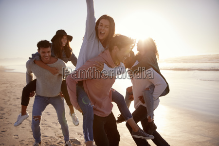 group of friends having piggyback race