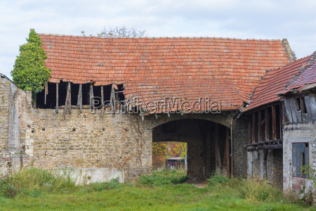 old stone barn with broken corrugated