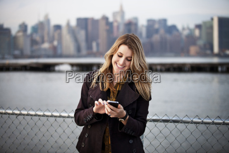 happy young woman using phone against