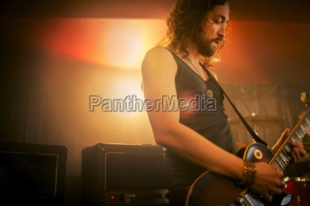 man practicing guitar in rock music