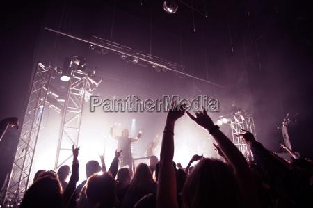 happy audience enjoying rock music concert