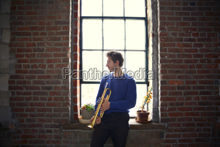 man with trumpet looking away while