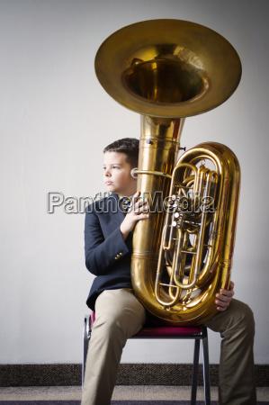 thoughtful boy holding tuba while sitting