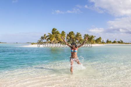 happy woman splashing water in lagoon