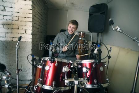 happy man playing drum kit at