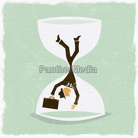 businessman falling in hourglass