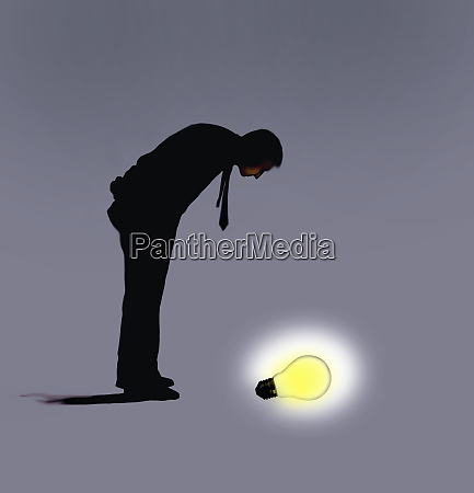 man looking down on glowing light