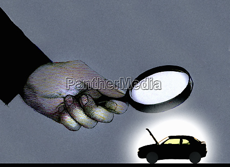 hand holding magnifying glass over car