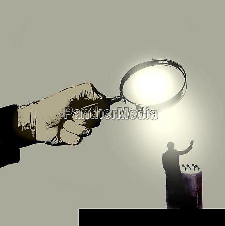 hand holding magnifying glass over politician