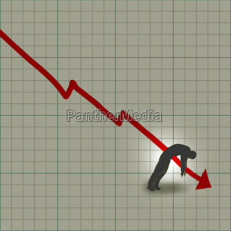 businessman impaled by decreasing line graph