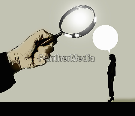 magnifying glass examining what businesswoman is
