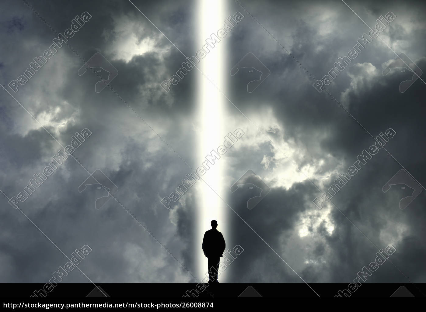 man, standing, in, shaft, of, light - 26008874