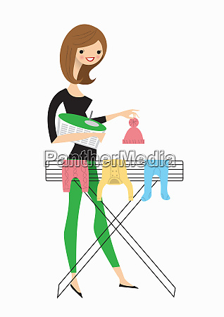 woman hanging baby clothes on airer