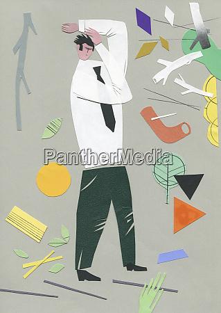 businessman shielding against wind blowing leaves