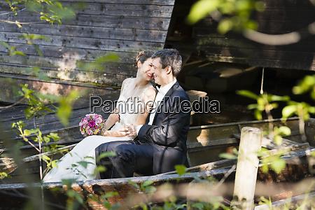smiling newlywed couple romancing while sitting