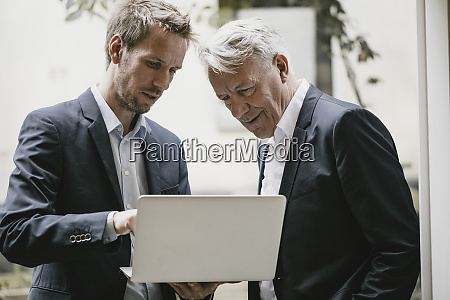 two businessmen standing in office using