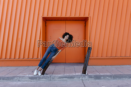 afro, woman, leaning, on, metal, against - 28763264