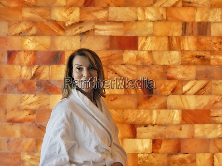 senior woman standing against wall at
