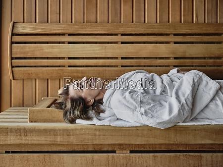 senior woman reclining on wooden sauna