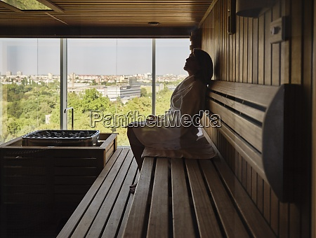 senior woman sitting on wooden sauna